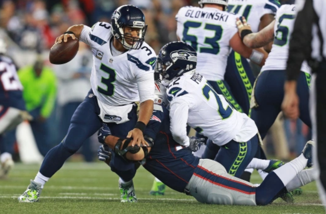 Russell Wilson Heading The Ball Against The Opponent