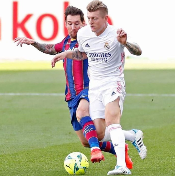 Toni Kroos heading the ball against the opponent, Lionel Messi